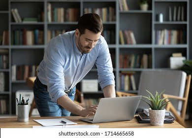 Confident businessman wearing glasses standing at desk, working online, focused serious man looking at computer screen, searching information in internet, writing business email to partner