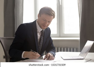 Confident businessman wearing suit signing contract or agreement, executive writing in official company documents at work, employee sitting at office desk with laptop, filling paperwork
