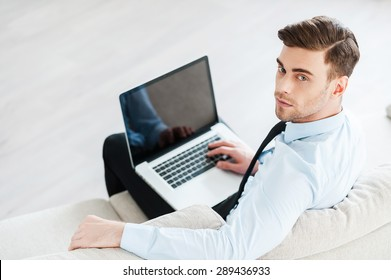 Confident businessman at work. Top view of confident young man working on laptop while sitting on sofa