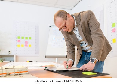 Confident businessman writing on notepad while standing at desk in office