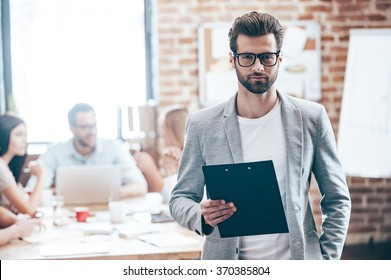 Confident businessman. Young handsome man holding notepad and looking at camera while his colleagues discussing something in the background