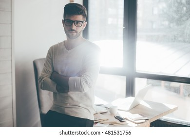 Confident businessman. Confident young man in eyeglasses keeping arms crossed and looking at camera while leaning at the desk in office