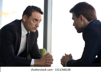 Confident businessmen with clasped hands sitting opposite, debate concept, business partners negotiations, difficult interview, negotiators conflict, confrontation, struggle for leadership at work