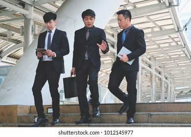 Confident businessmen in suit walking on the street, businessmen in suit looks away on background of steps of building, men with confident faces in formal suits and ties talking together
