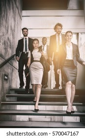 Confident businesswoman with colleagues climbing stairs in office