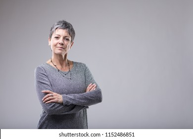 Confident businesswoman with folded arms standing looking intently at the camera over grey with copy space