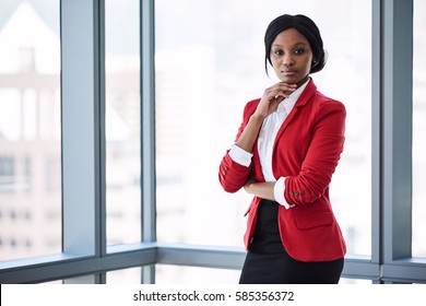 Confident businesswoman looking at the camera with bold body language while wearing a red blazer with large windows behind her in the background.