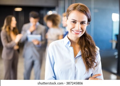 Confident businesswoman in office with her team in the background