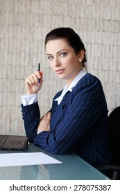 Confident businesswoman with pen, blank paper and laptop in office