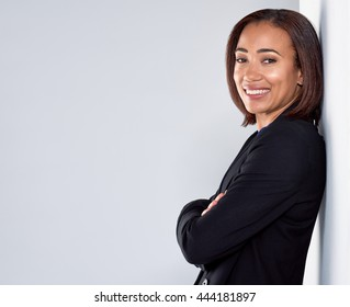 Confident businesswoman portrait wearing a black suit, smiling with arms crossed leaning against wall