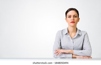 Confident businesswoman sitting at desk with folded hands. Young caucasian female student has serious facial expression. Portrait of girl wears shirt on white background. People emotion and expression