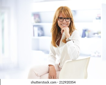 Confident businesswoman sitting at desk in office. Business people.
