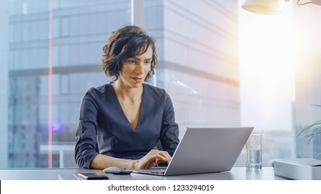 Confident Businesswoman Sitting at Her Desk and Working on a Laptop in Her Modern Office. Stylish Beautiful Woman Doing Important Job. In the Window Big City Business District View with Sun Flare.