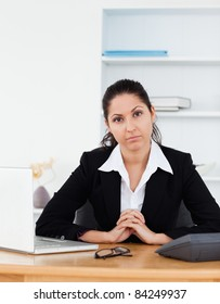 A confident businesswoman is sitting in her office