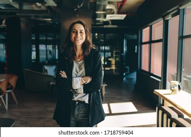 Confident businesswoman standing in office. Smiling woman standing with her arms crossed looking at camera.