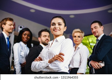 Confident Businesswoman Stands In Front Of Her Colleagues. Portrait Of Beautiful Woman With Crossed Hands Standing In Front Of Her Team. Blurred Image Of Business People On The Background,