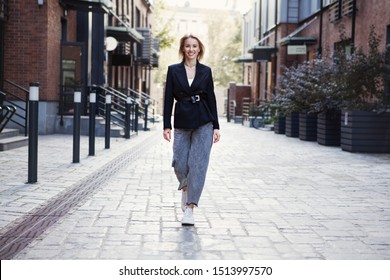 Confident Businesswoman In Stylish Office Clothes walking city street. Beautiful Smiling Woman Going To Work, Wearing Style Fashionable Spring, fall black jacket, oversize slouchy jeans. Autumn trend