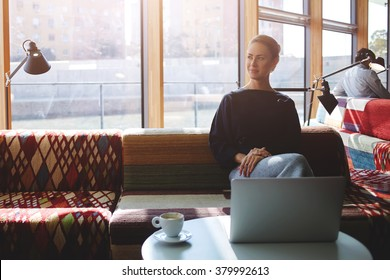 Confident businesswoman thinking about future meeting with partners while sitting with net-book in modern coffee shop, young female relaxing after work on laptop computer during coffee break in cafe