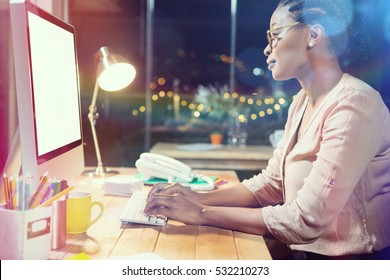 Confident businesswoman working on computer at desk in office