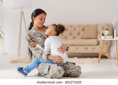 Confident caring mom holding her little girl in her arms