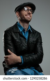 confident casual man in leather jacket looks up to side while smiling and sitting on light grey background