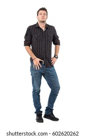 Confident casual man in plaid shirt and jeans with hand on belt looking at camera. Full body length portrait over white studio background.
