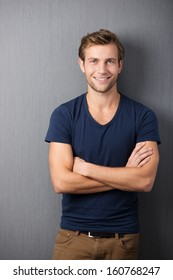 Confident casual unshaven young man standing with his arms folded looking at the camera with a wide friendly smile