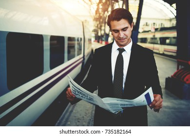 Confident caucasian businessman read financial newspaper while standing on railway station waiting train