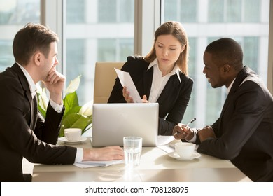 Confident caucasian businesswoman showing document with financial indicators, presenting project to african american colleague during negotiations in meeting room at office. Planning business strategy