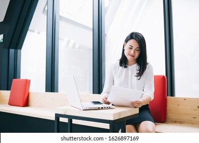 Confident caucasian female economist analysing report about company income holding papers and using laptop computer for job, 30s concentrated prosperous businesswoman reading contract in office