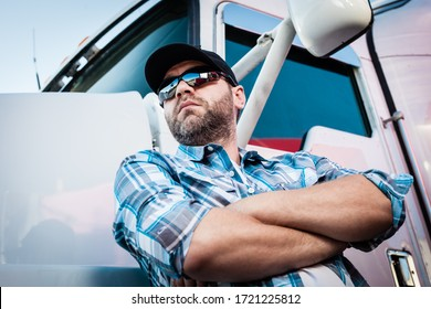 Confident Caucasian male american trucker next to his big rig. Concept of trucking owner operators with man in plaid shirt and baseball cap. Transportation industry professional 18 wheeler driver.