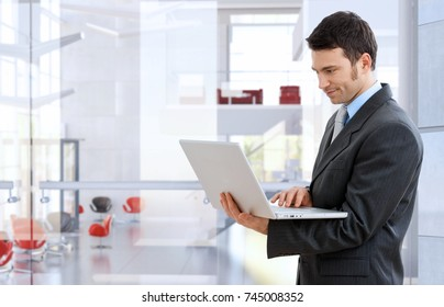 Confident caucasian stock broker standing and working with laptop at bright business office. Smirking, standing, suit and tie,
