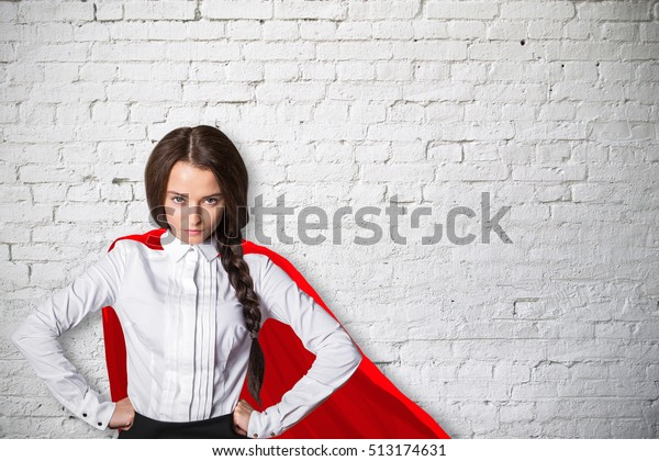 Confident caucasian superwoman with red cape on white brick wall background. Power concept