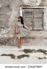 A confident Caucasian woman in a polka-dotted flowy dress and sunglasses posing outside