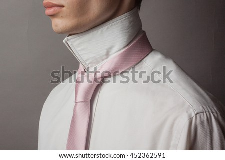 44db620780538a confident Caucasian young man a man in a white shirt with a raised collar  and a