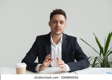 Confident CEO looking at camera talking about company strategy and business plan, explaining corporate success. Young entrepreneur shooting for online webinar, recording video blog. Headshot portrait