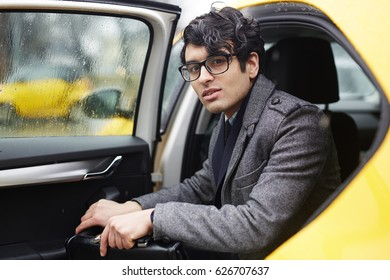 Confident ceo opening taxi cab door and getting out of it