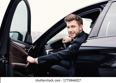 Confident Chauffeur. Guy in suit sitting in driver's seat, getting in his car at downtown area, closing the door