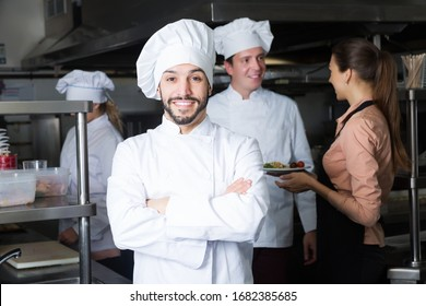 confident cheerful adult chef in kitchen with staff of restaurant