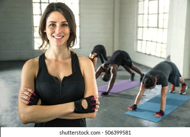 Confident cheerful beautiful physical fitness exercise trainer portrait with class smiling successful