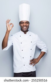 Confident chef. Confident young African chef in white uniform gesturing OK sign and smiling while standing against grey background
