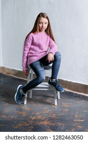 Confident child girl sitting fashion pose on chair,concrete white background. Stylish model in pink sweater. Beautiful glamorous kid teenager in clothes casual,urban style. Studio shot.