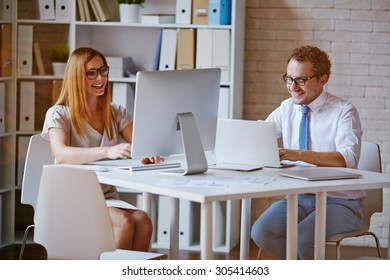 Confident colleagues computing in office