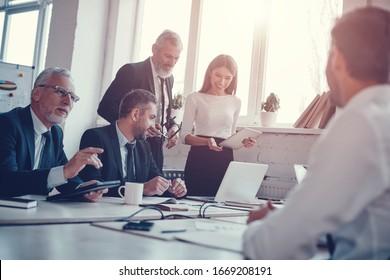 Collègues confiants discutant de l'extension de l'activité tout en travaillant ensemble dans le bureau moderne