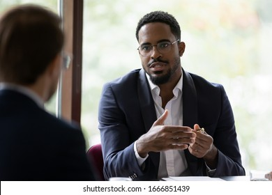 Confident concentrated African American male employee talk with colleague explain thought or idea, focused biracial businessman speak with coworker or partner, brainstorm at office boardroom meeting