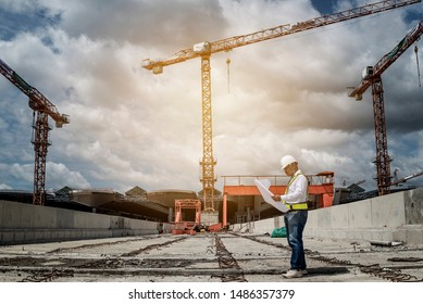 Confident construction engineer in hardhat with using cell phone on  construction background