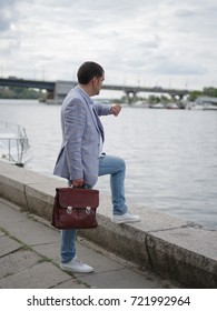 A confident corporate director looking at the watch blurred river background. Business man waiting on the urban coast. A middle-aged worker in a casual suit and short haircut. Copy space.