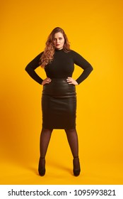 Confident curvy girl standing with her hands on hip