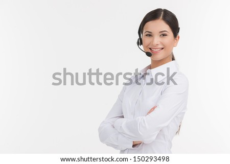 Confident customer service representative. Beautiful young female customer service representative in headset holding her arms crossed and looking at camera while isolated on white