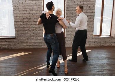 Confident dance instructor teaching aged people waltz in the ballroom